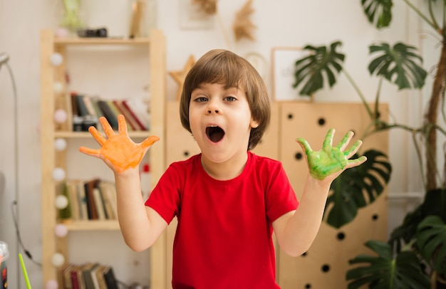 Happy little boy with painted hands sits at a table in a room and looks at the front