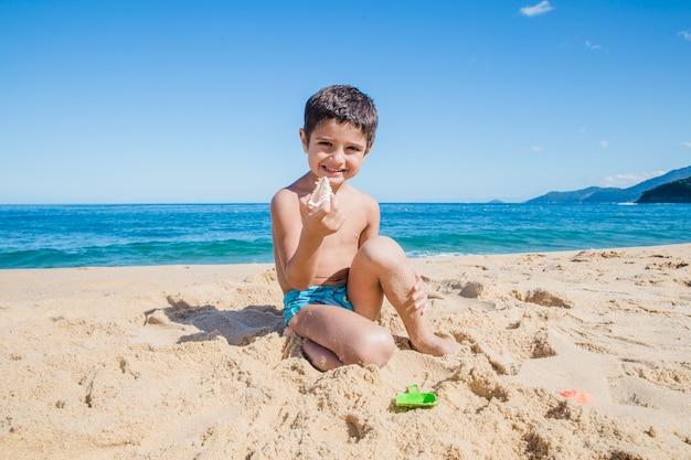 Felice ragazzino con guscio sulla spiaggia