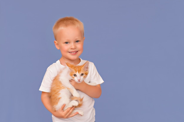 Happy little boy with a smile holds in his hands a little ginger kitten on a blue background