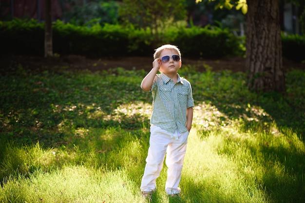 Счастливый маленький мальчик с очками в саду.