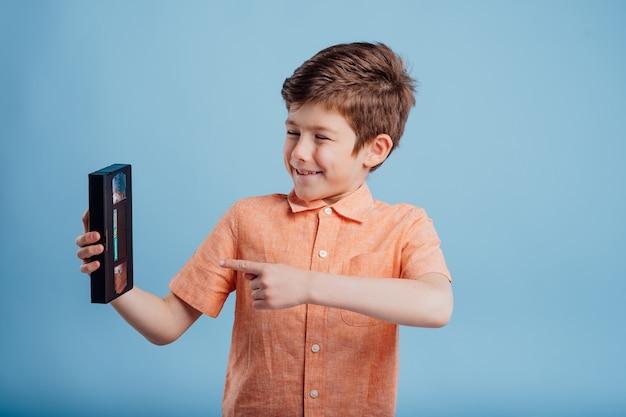 파란색 배경 오래된 가제트에 격리된 비디오 테이프를 가진 행복한 어린 소년