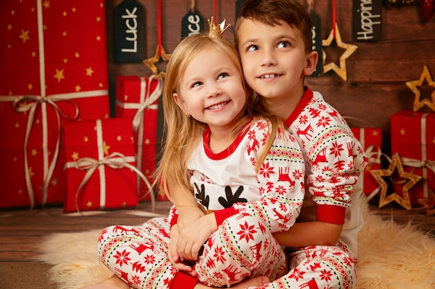 Happy little brother and sister in christmas pajamas waiting for gifts on christmas eve