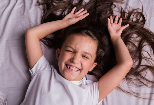 A happy little brunette girl in pajamas is lying on the bed linen on the bed with her eyes closed