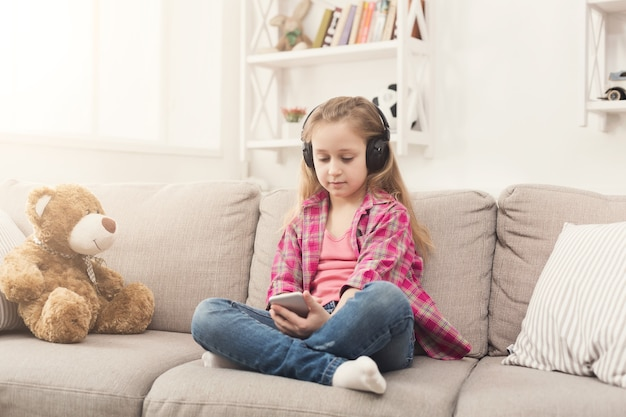 Happy little casual girl in headphones listening to music on smartphone. pretty kid at home watching cartoon on mobile phone online, sitting on sofa with her teddy bear, copy space