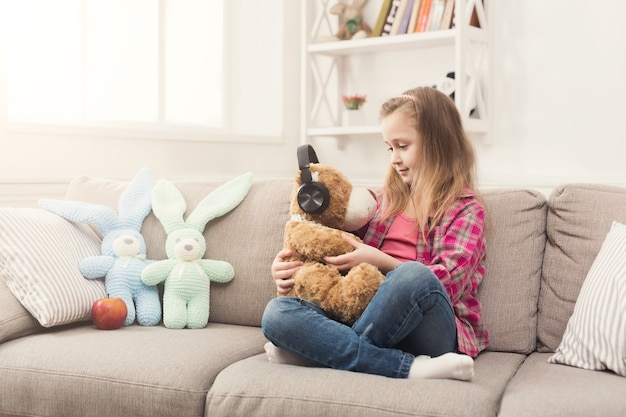 Happy little casual girl holding her teddy bear in headphones. pretty kid at home, sitting on sofa with favorite toy and listen to music, copy space