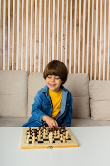 Happy little caucasian boy with brown hair is sitting on a sofa playing chess. child development