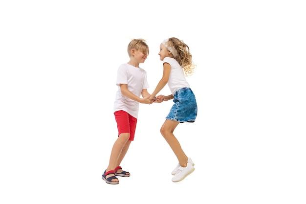 幸せな小さな白人の女の子と少年が白い背景で隔離のジャンプと実行