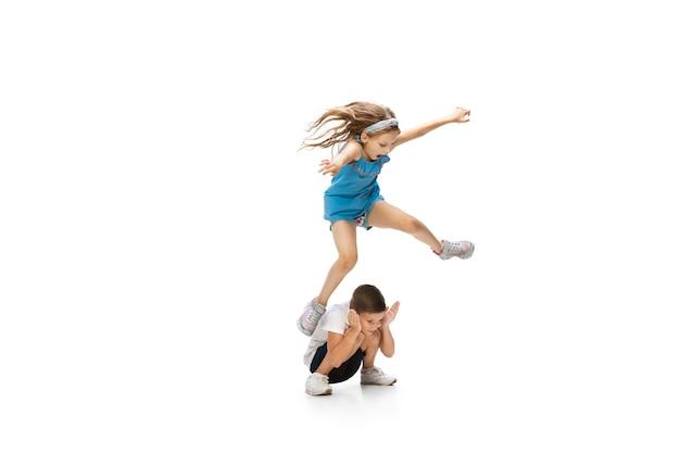 행복 한 작은 백인 소녀와 소년 점프 하 고 실행에 격리 된 흰색 배경