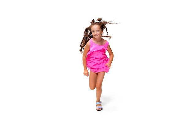 幸せな小さな白人の女の子が白で隔離のジャンプと実行