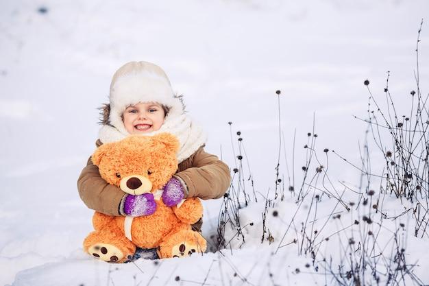 Счастливая маленькая кавказская девочка сидит на снегу и держит оранжевого плюшевого мишку.