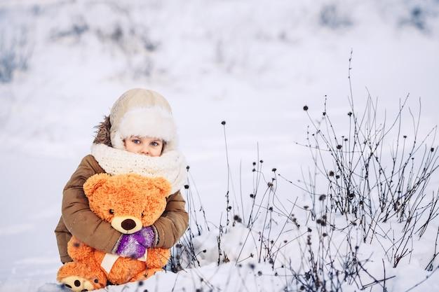 雪の上に座って、オレンジ色のテディベアを持って幸せな小さな白人の女の子