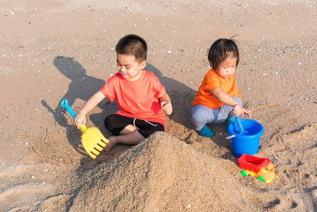 Happy little cheerful brother and sister two children funny digging play toy with sand at the beach