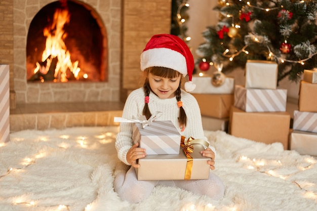 Happy little child by fireplace on christmas eve sitting on floor on soft carpet with two present boxes, looking at her gifts with happy expression, wants opening them, wearing casual clothing and hat