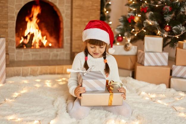 행복 한 표정으로 그녀의 선물을보고, 두 개의 선물 상자와 함께 부드러운 카펫에 바닥에 앉아 크리스마스 이브에 벽난로에 의해 행복한 작은 아이, 캐주얼 의류와 모자를 입고 그들을 열고 싶어