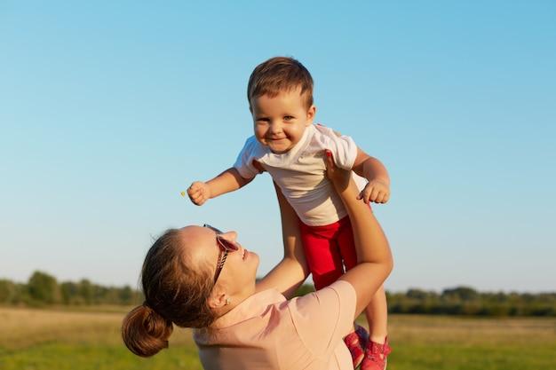 Счастливый маленький ребенок, летящий в небе в руках матери, выглядит счастливым и улыбается, привлекательная молодая мама подбрасывает ребенка в небе, наслаждаясь солнечным днем и красивой природой.