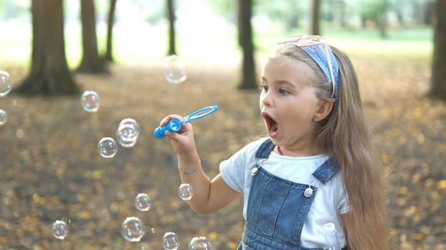 Happy little child girl blowing soap bubbles outside in green park