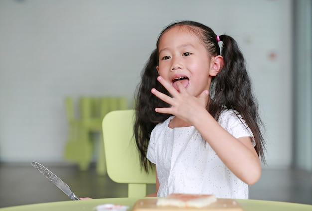 Happy little child girl cooking at classroom