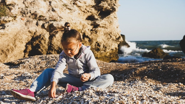 夏休みを楽しんで、ビーチで貝殻を遊んで幸せな小さな子の女の子。