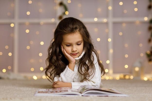 幸せな小さな子供の女の子はおとぎ話の本を読んでいます