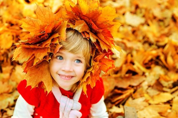 Счастливая маленькая девочка смеется осенью на открытом воздухе