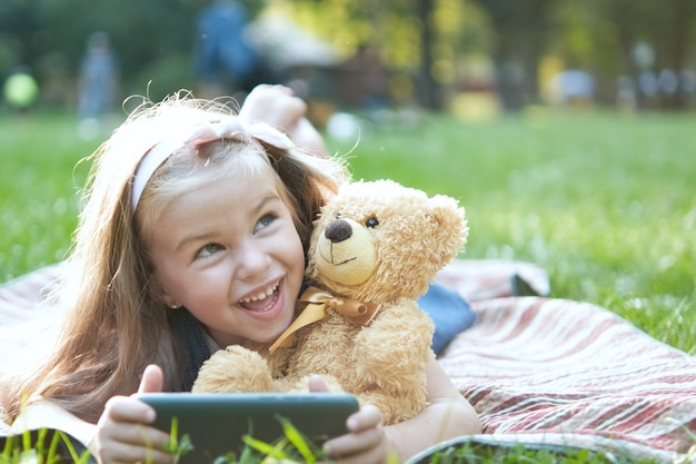 Happy little child girl looking in her mobile phone with her favorite teddy bear toy outdoors in summer park.