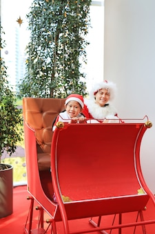 Happy little child girl and mom in santa costume dress sitting on red sledge