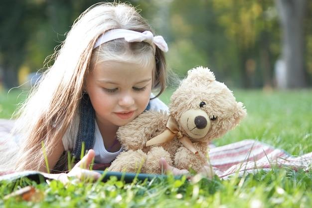 여름 공원에서 야외에서 좋아하는 테디 베어 장난감과 함께 그녀의 셀폰을 연주하는 행복한 어린 소녀.