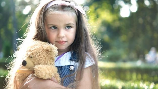 여름 공원에서 야외에서 그녀가 가장 좋아하는 테디 베어 장난감을 가지고 노는 행복한 어린 소녀.