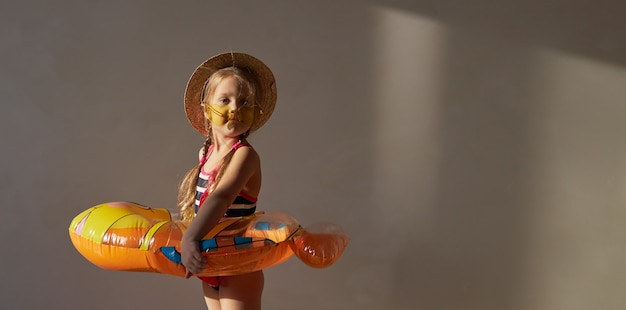 Happy little child girl in a swimsuit and a straw hat prepares for a summer trip at home.