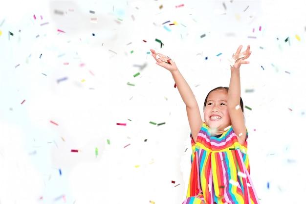 흰색 바탕에 화려한 색종이와 행복 한 작은 아이 소녀. 새해 복 많이 받으세요