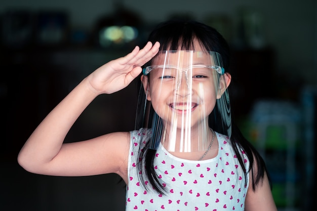 Happy little child girl with a plastic face shield for a virus protection mask on his face