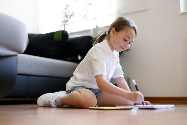Счастливый маленький ребенок удобно сидит на деревянном полу, рисует на бумаге цветными карандашами