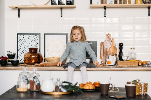 Happy little child in kitchen at home.