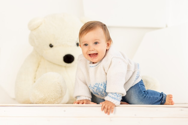 Happy little child in a knitted warm jacket and blue jeans crawls near large teddy bear