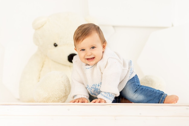A happy little child six months old in a knitted warm jacket and blue jeans crawls at home near a large teddy bear