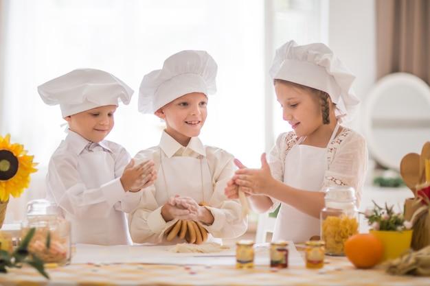 요리사의 형태로 행복한 어린 아이들이 맛있는 아침 식사를 요리합니다.