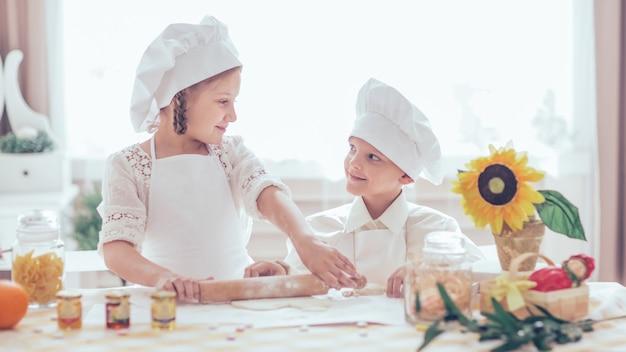 맛있는 요리를 준비하는 요리사의 형태로 행복한 어린 아이