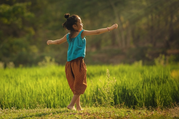 행복 한 작은 귀여운 아시아 어린이 소녀 검은 긴 머리 미소는 연주와 춤을 즐길 수
