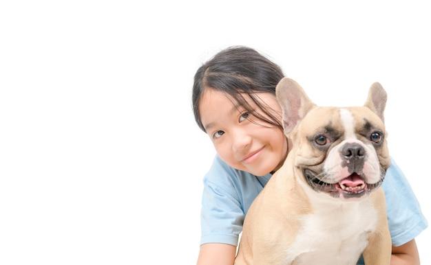 Счастливая маленькая милая девушка улыбается и играет с французским бульдогом, изолированным на белом фоне, домашних животных и концепции друга животных.