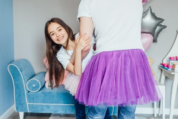 Piccola figlia felice che abbraccia il padre da dietro nella cameretta dei bambini