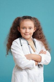 가슴으로 팔짱을 끼고 백의를 입은 행복한 작은 의사