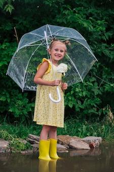 公園の夏の黄色のドレスと長靴で透明な傘を持つ幸せな小さな感情的な女の子