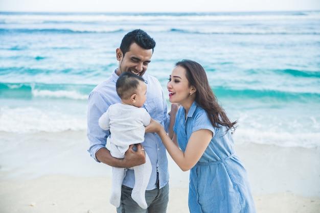 ビーチでかわいい息子の休暇で幸せな小さな家族