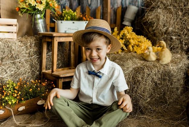 밀짚 모자에 행복한 작은 농부 소년은 헛간에 오리와 함께 빨대에 앉아
