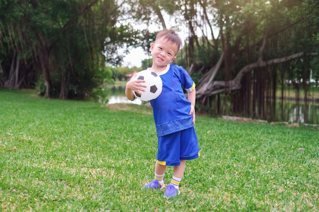 Happy little football player in soccer uniform is holding soccer ball