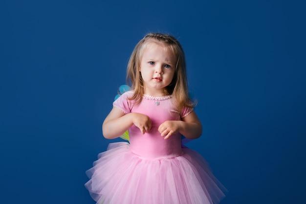 青のかわいいクリスマスピンクのポニー衣装で幸せな小さな面白い感情的な子供の女の子