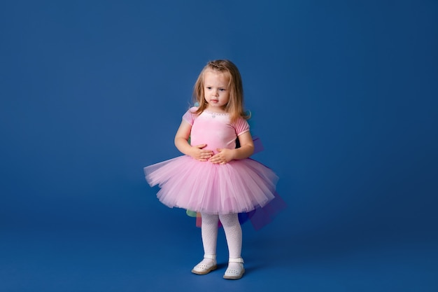 青い色の背景にかわいいピンクのポニーの衣装で幸せな小さな面白い感情的な子の女の子。