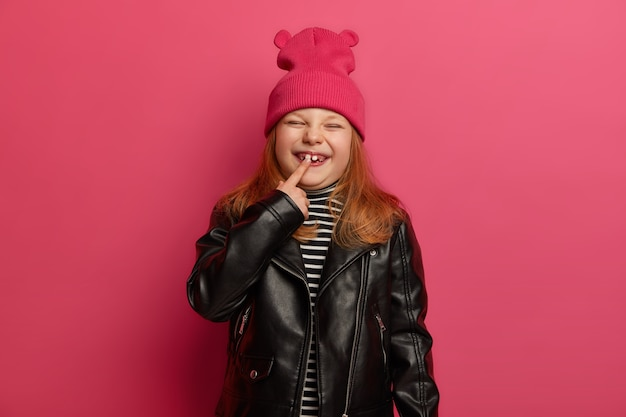 Happy little ginger girl in fashionabe clothes, indicates at her new tooth, has unforgettable childhood, squints face with pleasure, poses against briht pink wall. chidren growth concept