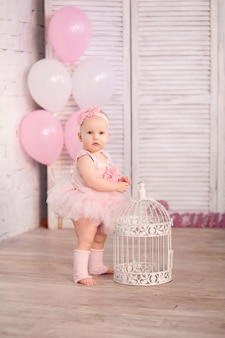Happy little girl 1 year old ballerina in studio on light wall with pink balls