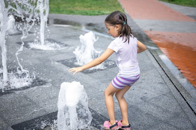 Bambina felice tra gli spruzzi d'acqua della fontana della città si diverte e fugge dal caldo.